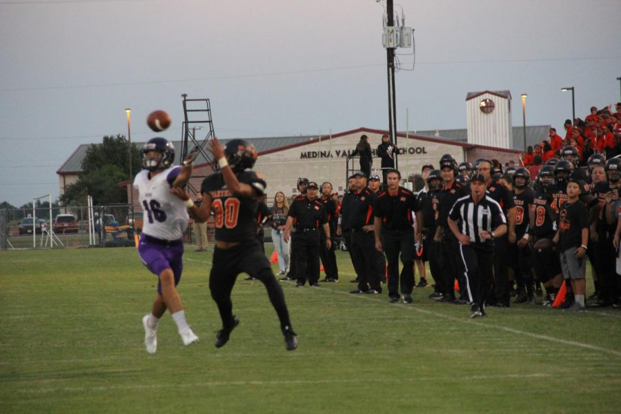 Caytan Chang attempting to turn a pass into a touchdown as the crowd watches on the edge of their seats.