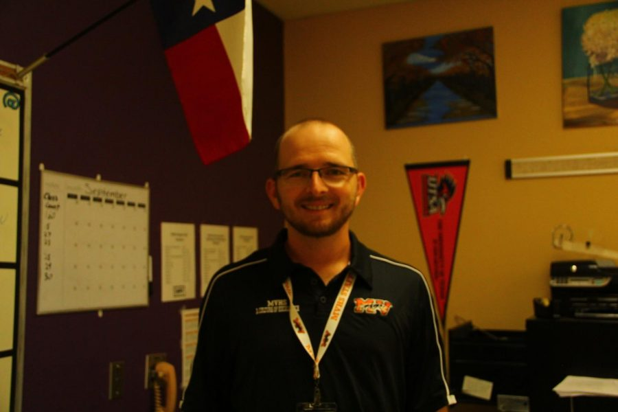 Mr. Campbell stands in his classroom in front of his UTSA pennant. PC: Mackenzie Noakes