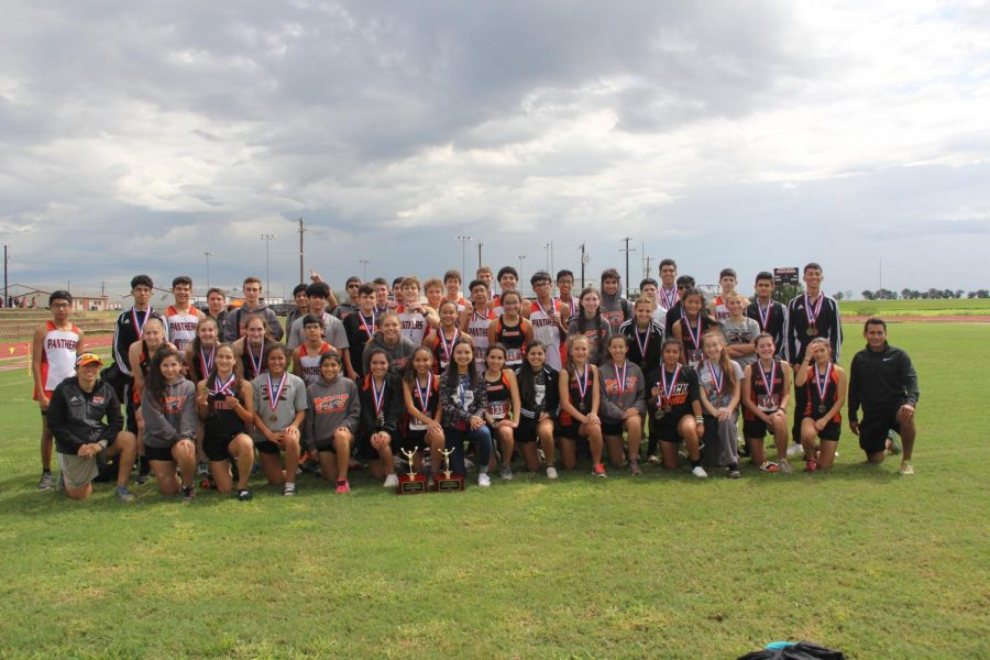 2018-2019 Cross Country team posing with coaches and District winning trophies.