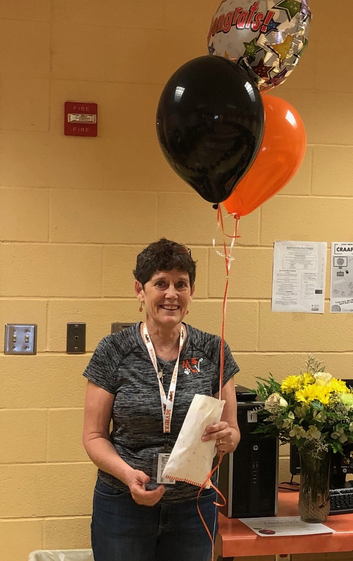 Mrs.Clary poses for a picture with her Congratulatory balloons and popcorn.  Picture Credit: Admin