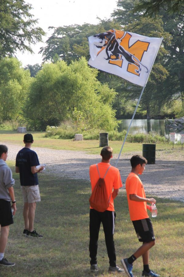 Junior Blake Mulvany hold the Medina Valley flag beside freshmen Timothy Teague cheering on the JV team as they ran by.