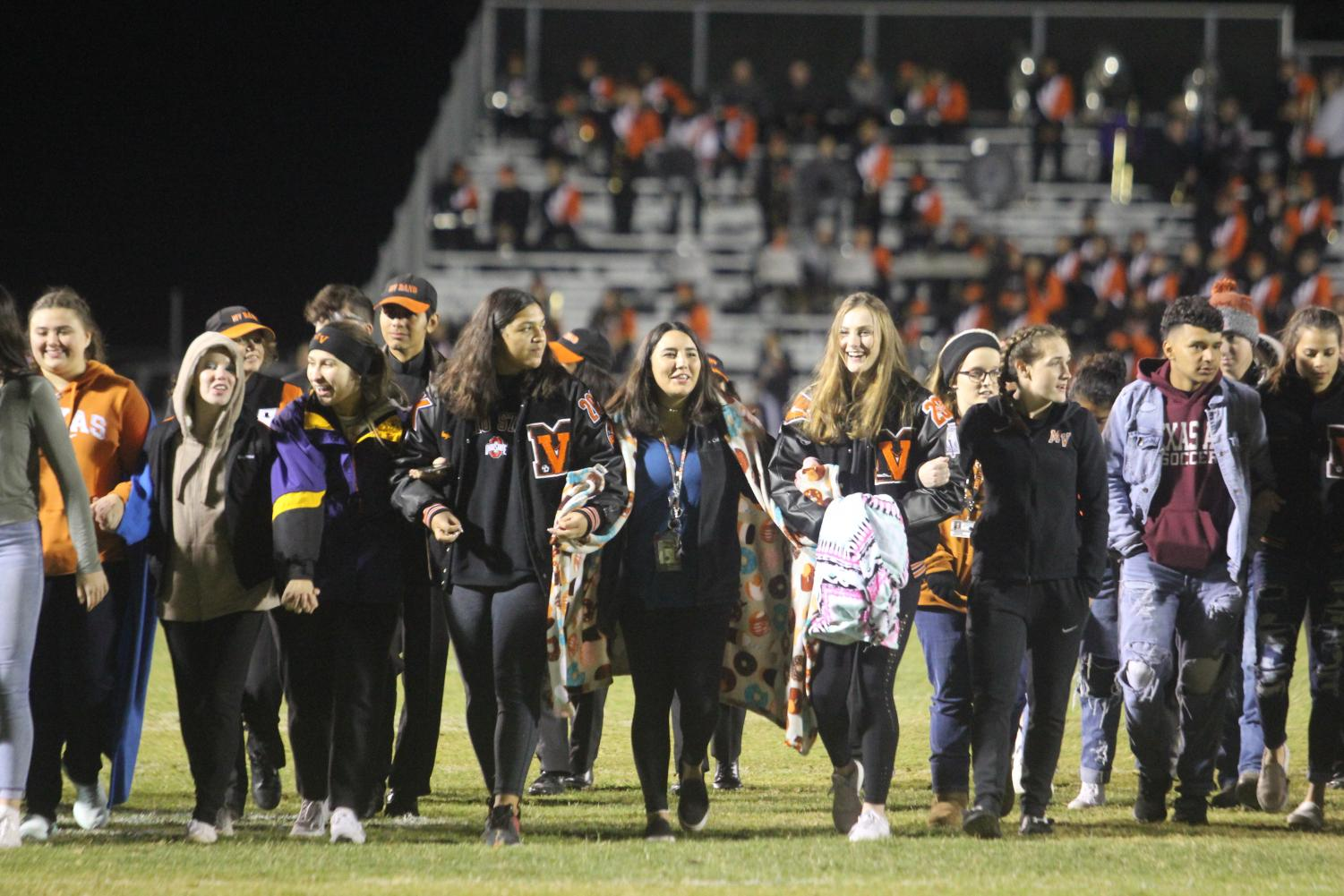 Seniors Link arms to walk the across the field