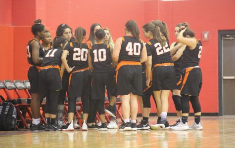 The JV girls basketball team getting a  talk from Coach Misti Kennitt before going out on the court.